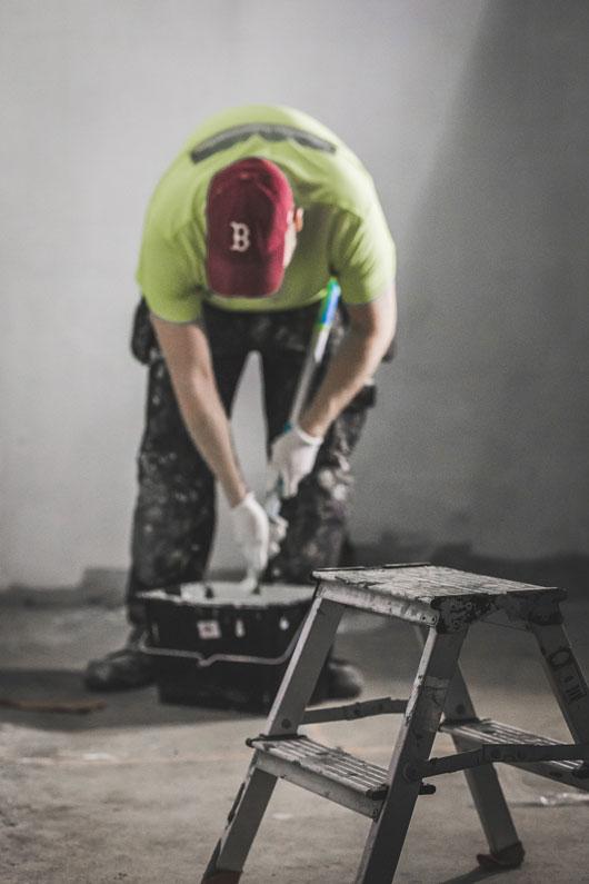 Maalari ottamassa astiasta lisää maalia telaan.